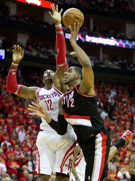 True to his word, Dwight Howard, left, makes it tough on the Blazers' LaMarcus Aldridge to get off a shot. Howard says that's the key to limiting Aldridge. Photo: Brett Coomer, Staff / © 2014 Houston Chronicle