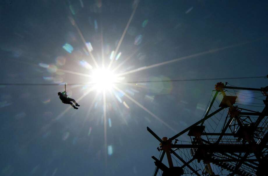 A rider dangles from a zip at Moody Gardens newest exhibit Moody Gardens Zip Line and Sky Trail Ropes Course during a media event highlighting the attraction Thursday, May 1, 2014, in Galveston. The zip line is the largest on the Gulf Coast at 81 feet tall. The ride opens May 3. Photo: Johnny Hanson, Houston Chronicle / © 2014  Houston Chronicle