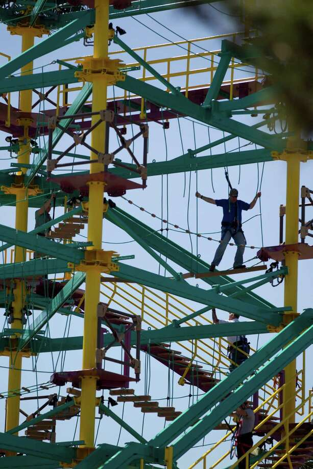 An attendee balances on a beam while holding onto ropes on the Sky Trail Ropes Course and Moody Gardens Zip Line. The Sky Trail Ropes Course included five tiers and 48 different obstacles. Photo: Johnny Hanson, Houston Chronicle / © 2014  Houston Chronicle