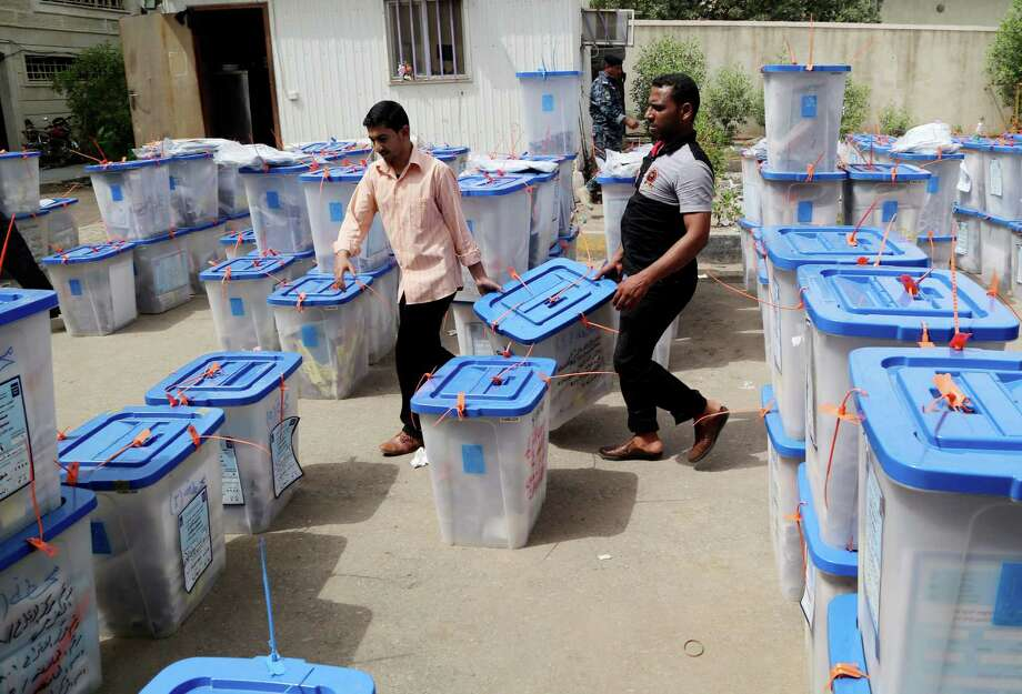 Electoral workers move ballot boxes at a counting center in Basra, Iraq's second-largest city, on Thursday. Counting the ballots in the nation's last election, four years ago, took about two weeks to complete. Photo: Nabil Al-Jurani, STF / AP