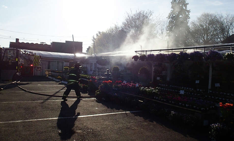 Firefighters tackle a fire that erupted at Izzoís Country Gardens and Landscaping, 1431 Post Road East, and prevented it from spreading beyond the main nursery building. Photo: Westport Fire Department / Westport News