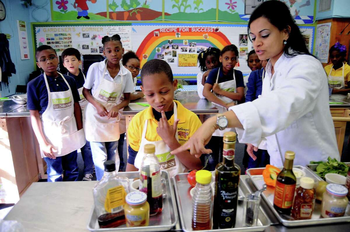 Instructor Priti Vakil shows Amir Bryant ingredients his group can use during the salad-making contest at McGregor Elementary School. The Iron Chef-style competition was part of the Recipe for Success program that includes 27 Houston-area schools.
