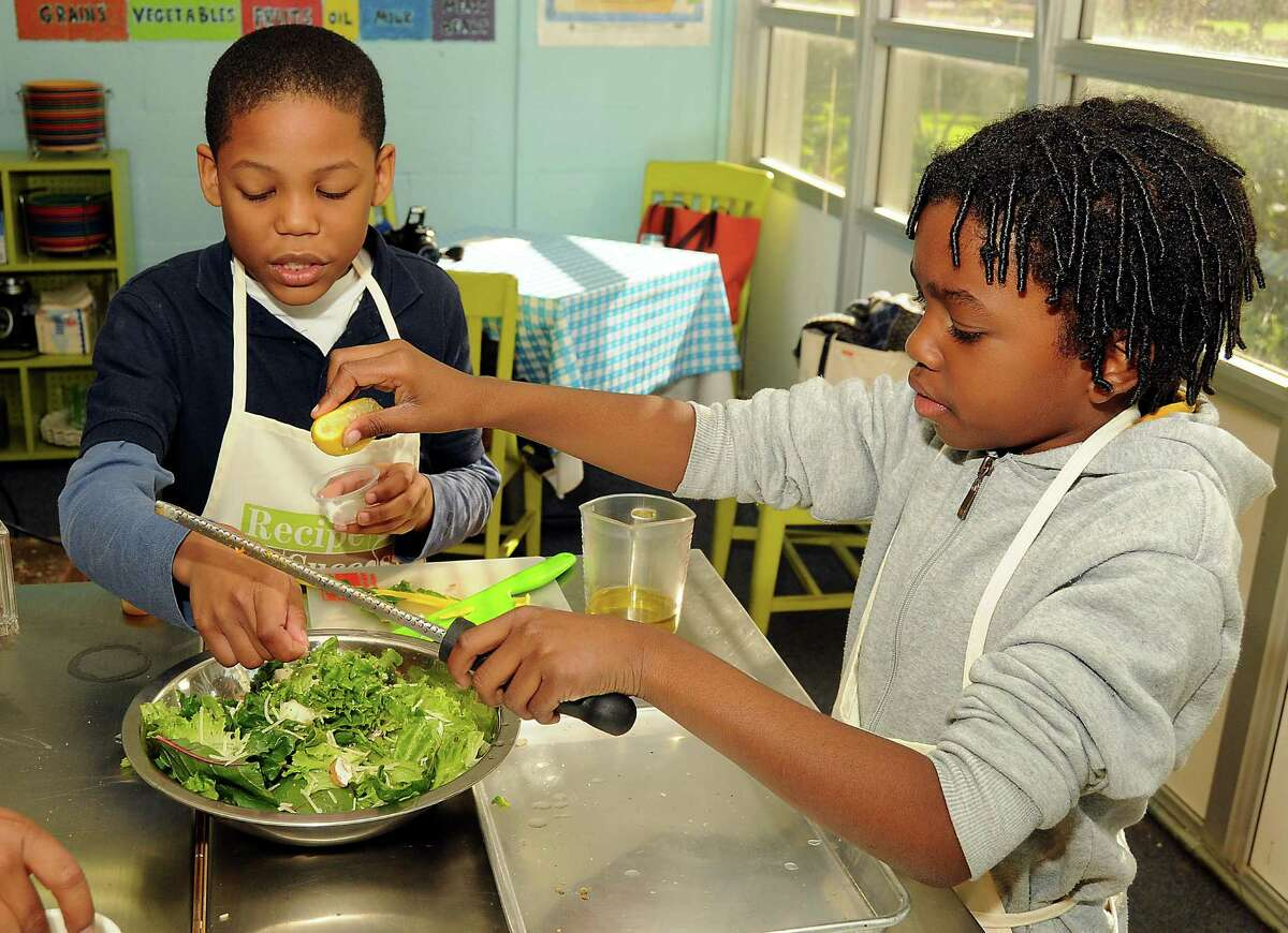 Zion Dulechain and Solomon Yero add some lemon zest during a salad-making contest Wednesday in the Recipe for Success program.