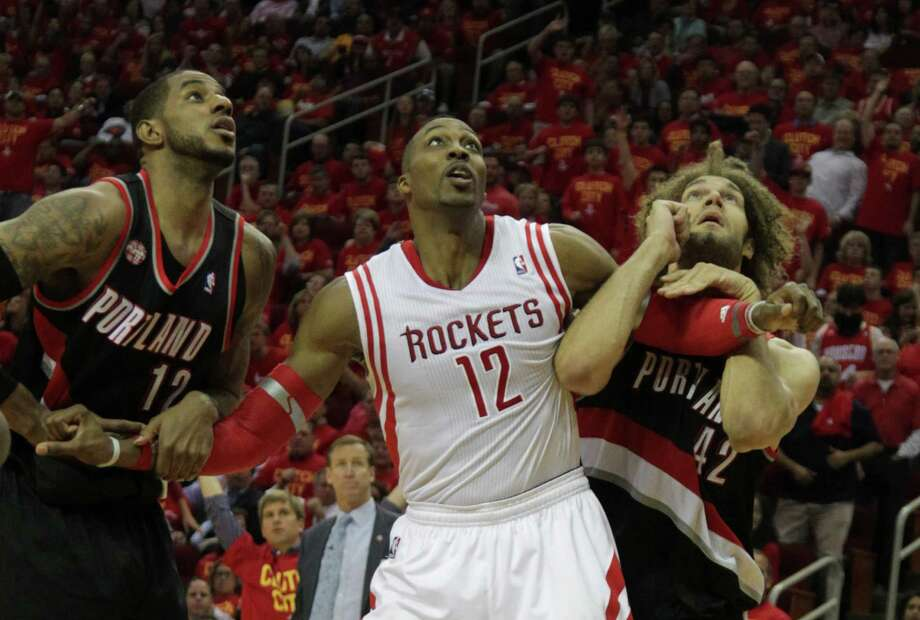 Even with the attention of LaMarcus Aldridge, left, and Robin Lopez, right, Dwight Howard is averaging 26 points and 14.2 rebounds. Photo: James Nielsen, Staff / © 2014  Houston Chronicle