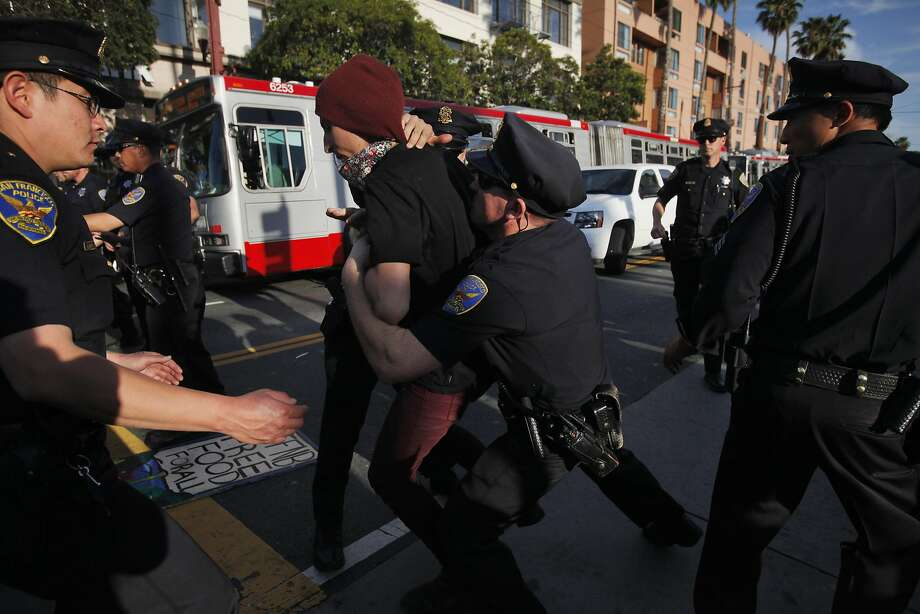 Police grab a protester as he tries to break through a circle of officers surrounding a small group of people from among the hundreds who had attended a May Day rally. The event was against evictions, gentrification and police brutality at 24th and Mission streets and moved to 16th Street, where multiple protesters were arrested. Photo: Leah Millis, San Francisco Chronicle