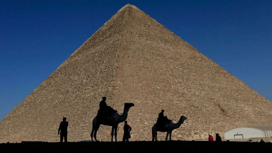 Policemen are silhouetted against a pyramid in Giza, Egypt. Photo: Hassan Ammar, Associated Press