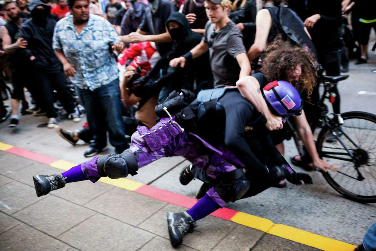 A man dressed up in superhero garb is thrown to the ground by a protester in a tussle during a May Day anti-capitalist march Thursday, May 1, 2014, in Seattle, Wash. No arrests were made in regards to the fight.