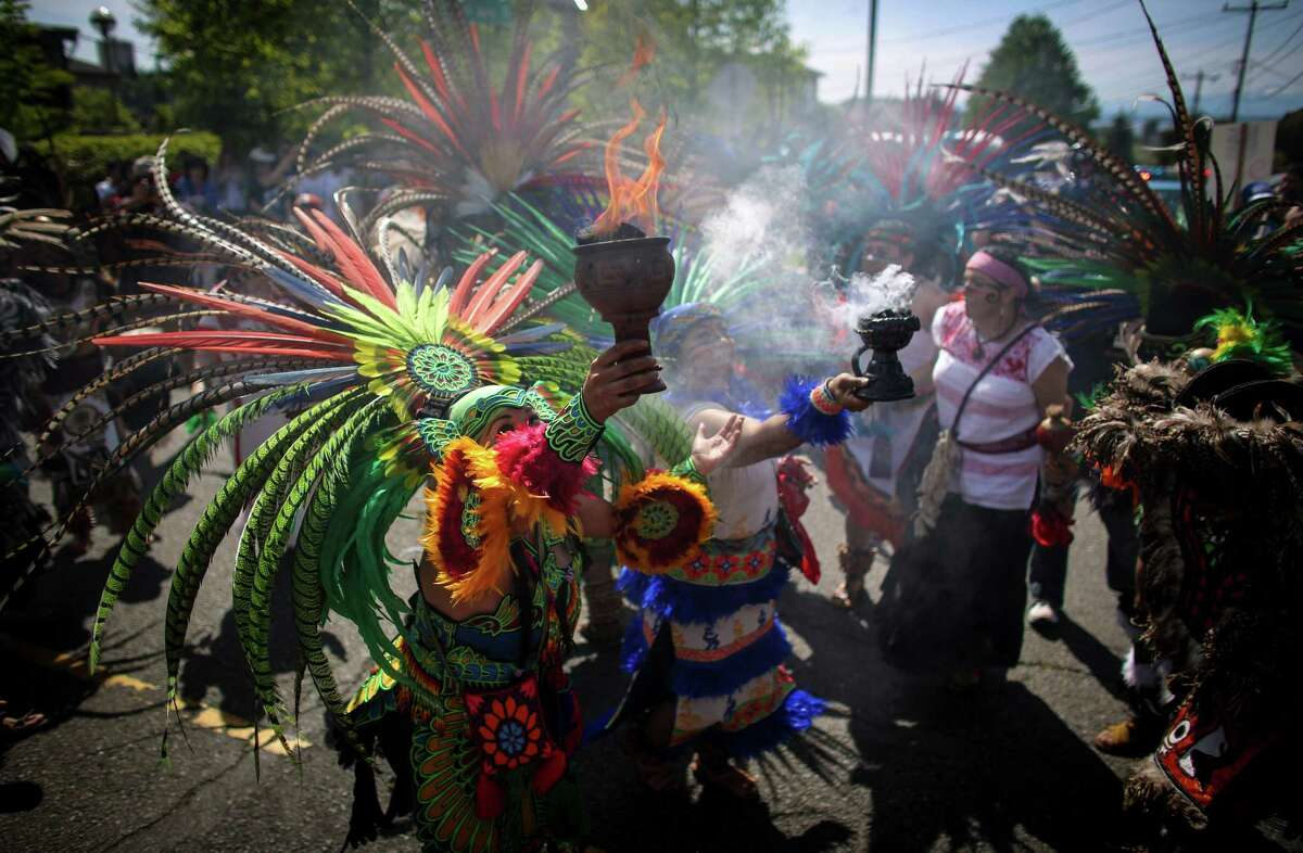 Aztec dancers lead the way during a May Day immigration reform march on Thursday, May 1, 2014. Marchers called for a reform of the US immigration system and for a minimum wage of $15 per hour.