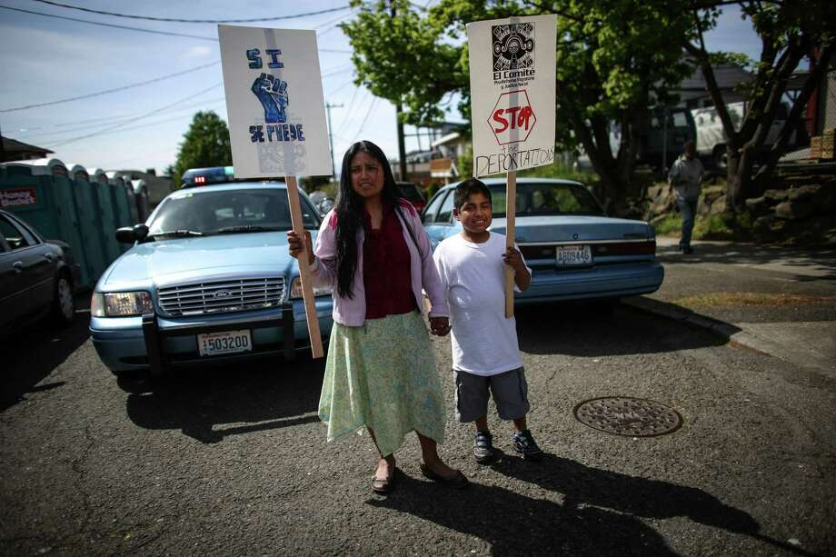 Teresa Huerta waits with her son Fernando Huerta Martinez, 8, during a May Day immigration reform march on Thursday, May 1, 2014. Marchers called for a reform of the US immigration system and for a minimum wage of $15 per hour. Photo: JOSHUA TRUJILLO, SEATTLEPI.COM / SEATTLEPI.COM