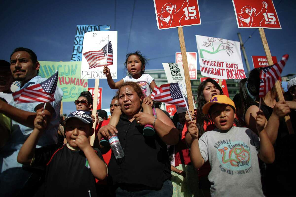 Itcel Bautista carries her daughter Yareci, 3, during a May Day immigration reform march on Thursday, May 1, 2014. Marchers called for a reform of the US immigration system and for a minimum wage of $15 per hour.