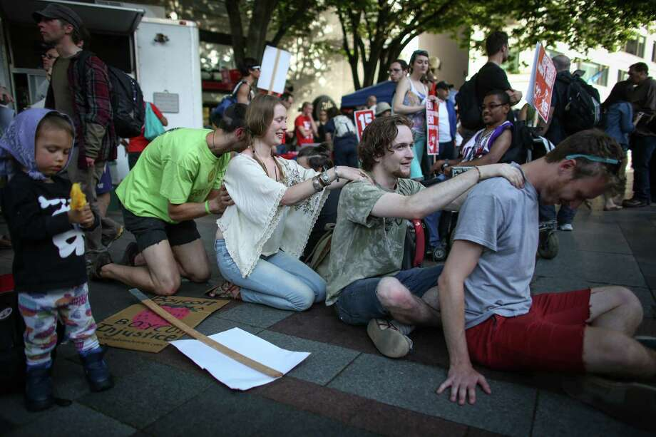 People give back massages at Westlake Park during a May Day immigration reform march on Thursday, May 1, 2014. Marchers called for a reform of the US immigration system and for a minimum wage of $15 per hour. Photo: JOSHUA TRUJILLO, SEATTLEPI.COM / SEATTLEPI.COM