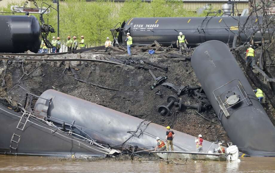 Workers remove damaged tankers along the tracks where several CSX crude oil cars derailed and caught fire along the James River near downtown Lynchburg, Va., Thursday, May 1, 2014. Photo: Steve Helber, AP