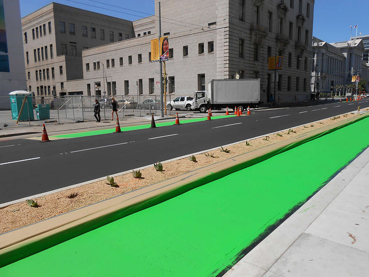 The new Polk contraflow bikeway is physically protected, offering a barrier between people biking and driving.