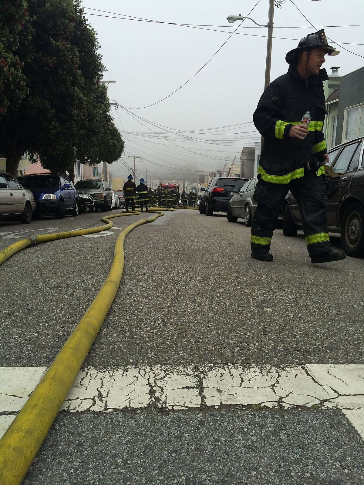 San Francisco firefighters at the scene of a blaze in the Oceanview neighborhood that injured two people and damaged four homes.