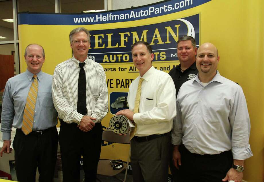 Enjoying the open house of Helfman Auto Parts were, from left to right, Pat Dougherty, Chrysler's vice president of Mopar sales; Tony Brenders, Chrysler's vice president of technical service operation; Steven Wolf, general manager of Helfman Dodge; Derrick Armfield, field representative for Magneti Marelli; and Sam Debner, Helfman Dodge's director of parts and business development.
