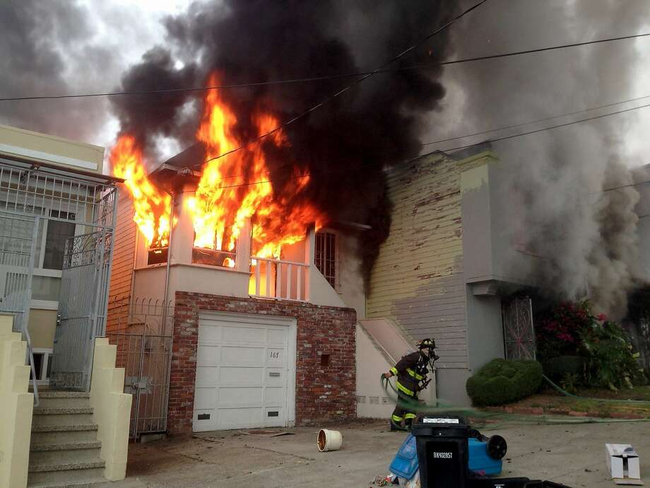 One of five homes damaged Friday morning in a fire in San Francisco's Oceanview neighborhood is shown totally involved in flames in this photograph by a Tianxing Wang, a neighbor whose home was also damaged. Photo: Wang Tianxing, Special To The Chronicle