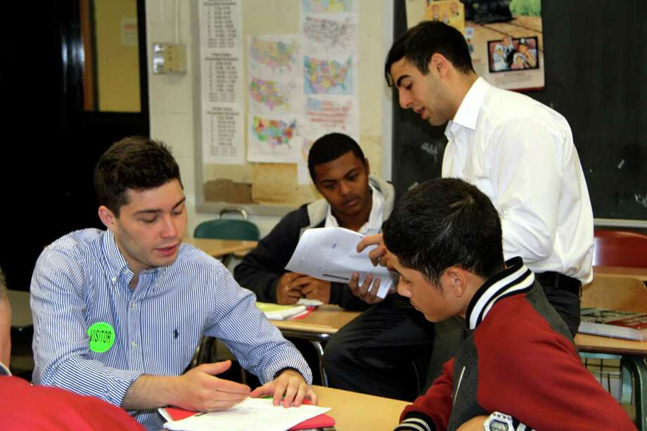 Fairfield University student Tyler Paci mentors Bridgeport Central High School student Nauel Tejada in a Network for Teaching Entrepreneurship, or NFTE, class taught by David Christy at Central HS  in Bridgeport, Conn. The University students, all enrolled at the Dolan School of Business, were working with the Central students to develop their business plans. The students got together on April 30, 2014. Also working on a presentation is Central student  Kareem Powell with the help of John Paul Sakakini. Photo: Contributed Photo, David Christy/Contributed Photo / Connecticut Post Contributed