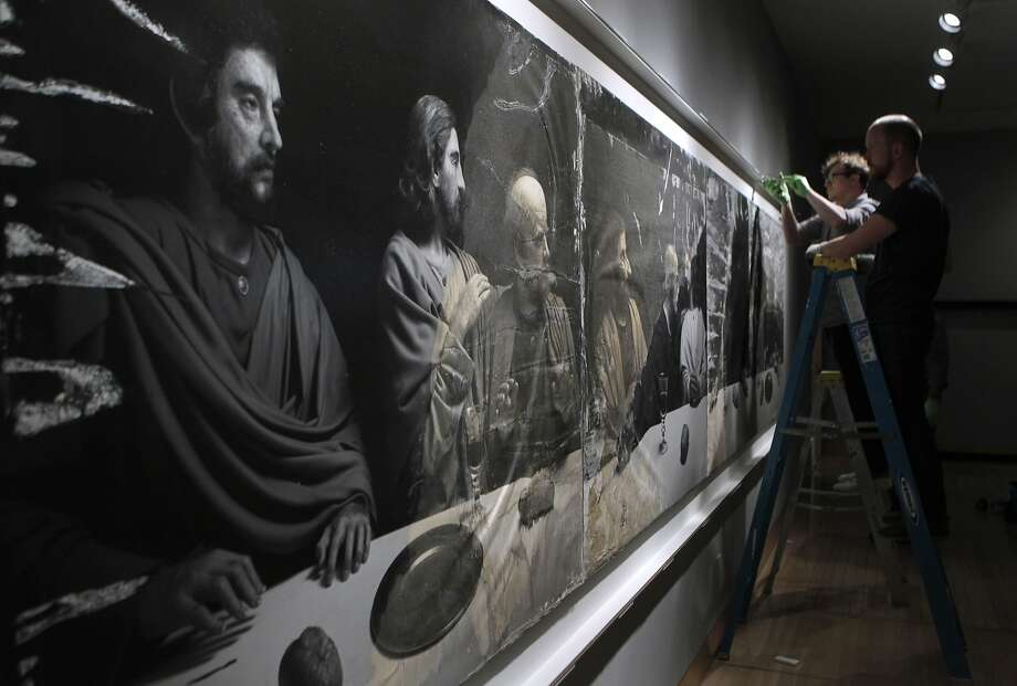 "Gregg Stanger and Keith Gidlund install a version of ""The Last Supper: Acts of God"" by photographer Hiroshi Sugimoto at Fraenkel Gallery in S.F. The mural was damaged by Hurricane Sandy. Photo: Paul Chinn, The Chronicle"