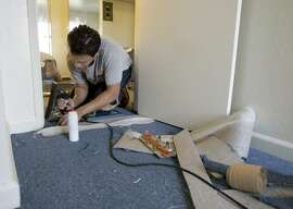 Albert Ullrich installs new carpet in one of the apartments. Volunteers from Rebuilding Together and Affordable Housing Associates prepared eight apartments which will be occupied by displaced evacuees from Hurricane Katrina on 9/30/05 in Berkeley, Calif. PAUL CHINN/The Chronicle