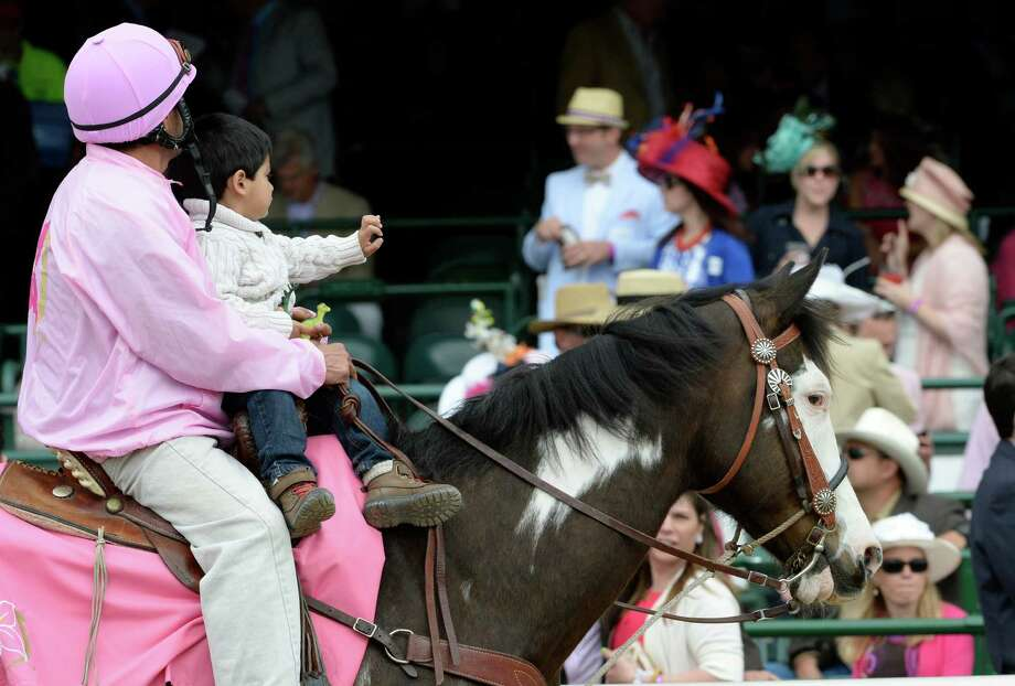 An outrider takes his child for ride in front of race fans Friday, May 2, 2014, at Churchill Downs Race Track, the home of the 140th running of the Kentucky Derby to be run Saturday in Louisville, Kentucky.   (Skip Dickstein / Times Union) Photo: SKIP DICKSTEIN