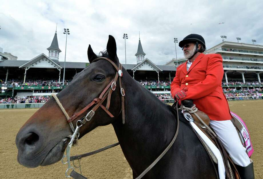 Outrider Kenny LaVergne of New Orleans watches for any problems on the track as he sits under the famed spires of Churchill Downs Race Track Friday, May 2, 2014, home of the 140th running of the Kentucky Derby to be run Saturday in Louisville, Kentucky.  (Skip Dickstein / Times Union) Photo: SKIP DICKSTEIN