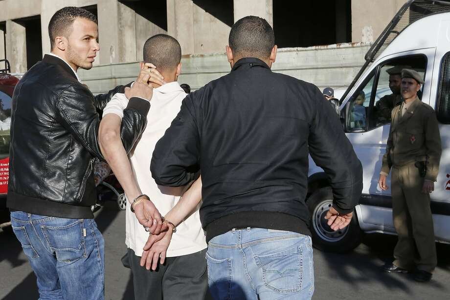 Plainclothes police officers escort a drug-dealer suspect after his arrest at Derb El Kabir, an area known for crime and drugs in Casablanca. The city of 3 million people has a long-standing crime problem. Photo: Abdeljalil Bounhar, Associated Press