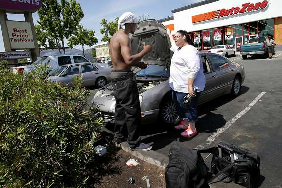 A mechanic named Solo Bolo (left) talks with a customer named Rene Roche about her air conditioning problem Wednesday April 30, 2014 in Oakland, Calif. His tools are in the foreground. A group of automobile mechanics work in the parking lot of the AutoZone at Bancroft and 73rd Avenue are doing various repairs for a fraction of the cost of a real-live certified mechanic.