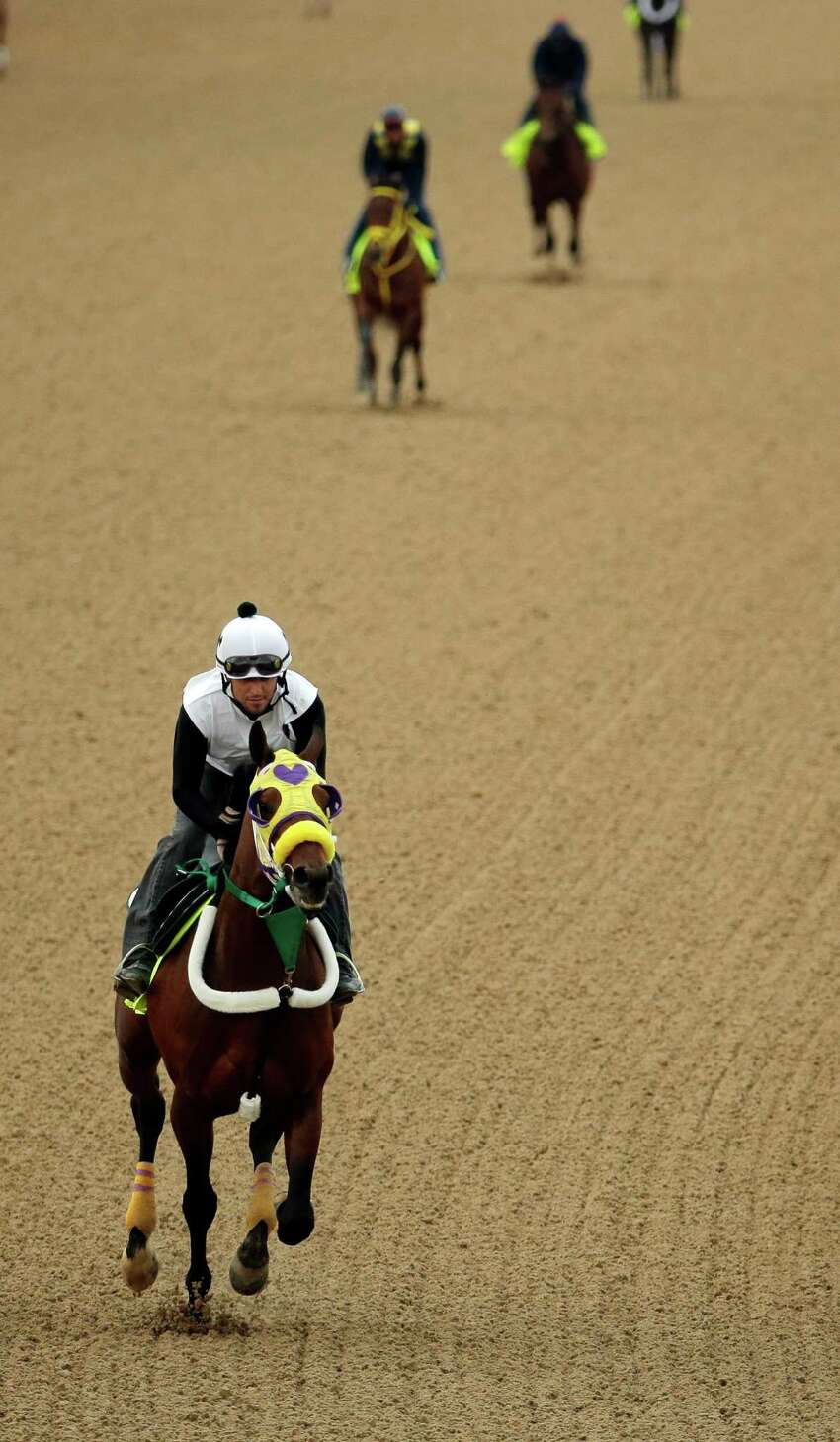 Exercise rider Benito Alvarado takes Kentucky Derby hopeful Uncle Sigh for a morning workout at Churchill Downs Wednesday, April 30, 2014, in Louisville, Ky. (AP Photo/Charlie Riedel) ORG XMIT: DBY127