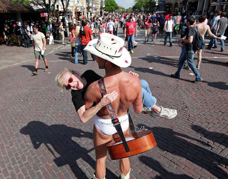 "FOR METRO - Loretta Lang, 73, is all smiles as she is carried by Robert ""The Naked Cowboy"" Burck on 6th Street during South by Southwest Thursday March 15, 2012 in Austin, TX. Photo: EDWARD A. ORNELAS, SAN ANTONIO EXPRESS-NEWS / © SAN ANTONIO EXPRESS-NEWS (NFS)"
