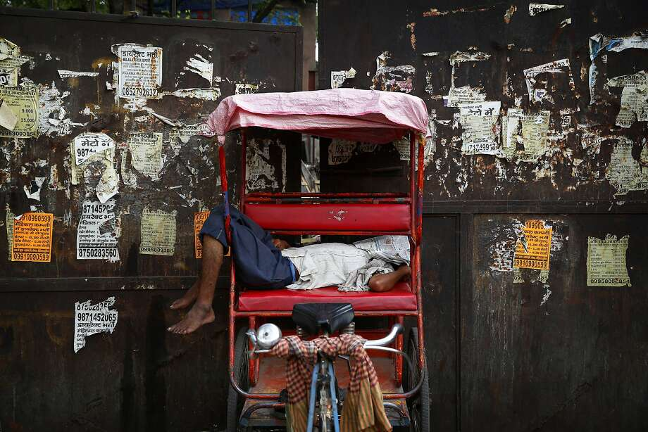 Too hot for a taxi: In New Delhi, an off-duty rickshaw operator naps in the midday heat. Temperatures 