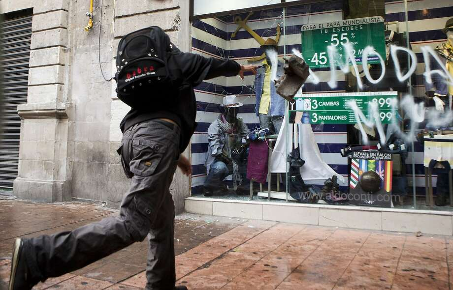 Down with commerce! An anarchist makes his political statement by smashing the store window of an unfortunate merchant during May Day in Mexico City. Thousands of people, many calling for greater 