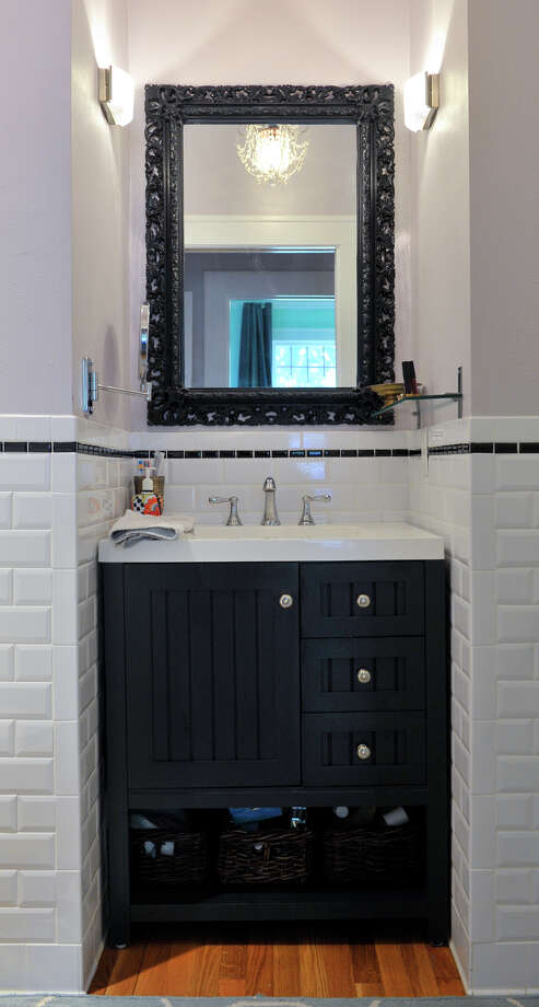 Ruthie Foultz expanded a cramped second bath that previously included only a shower and toilet by taking in a closet, walling off an entrance to the kitchen and putting a vanity there. Photo: Robin Jerstad, For The Express-News