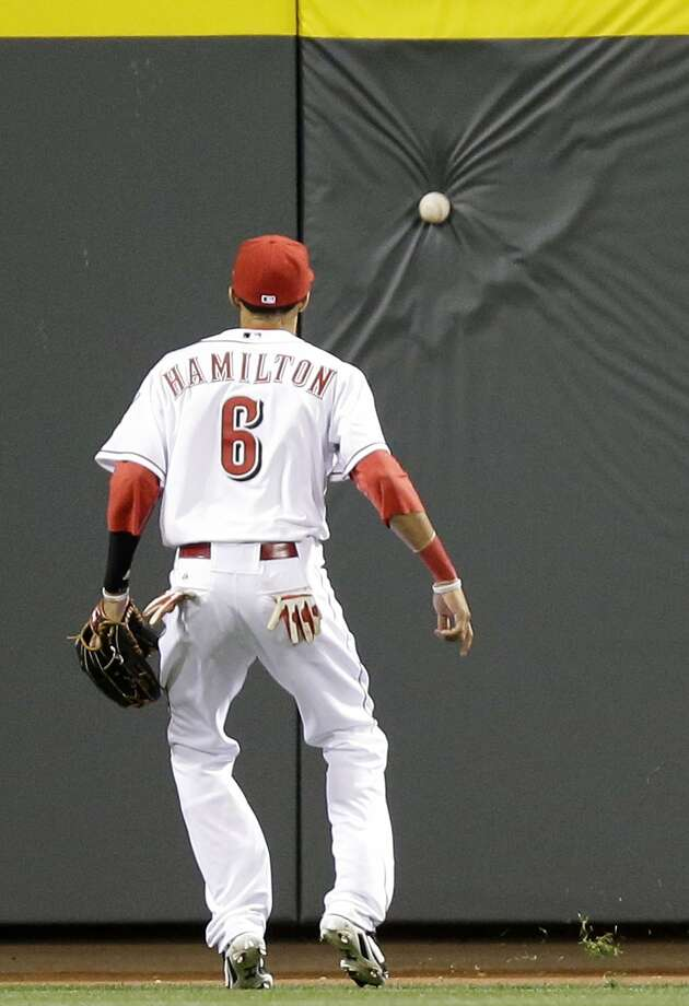 He hit the ball real hard:Reds center fielder Billy Hamilton watches as a long drive hit by the   Cubs' Starlin Castro appears to stick in the outfield wall in Cincinnati. Photo: Associated Press