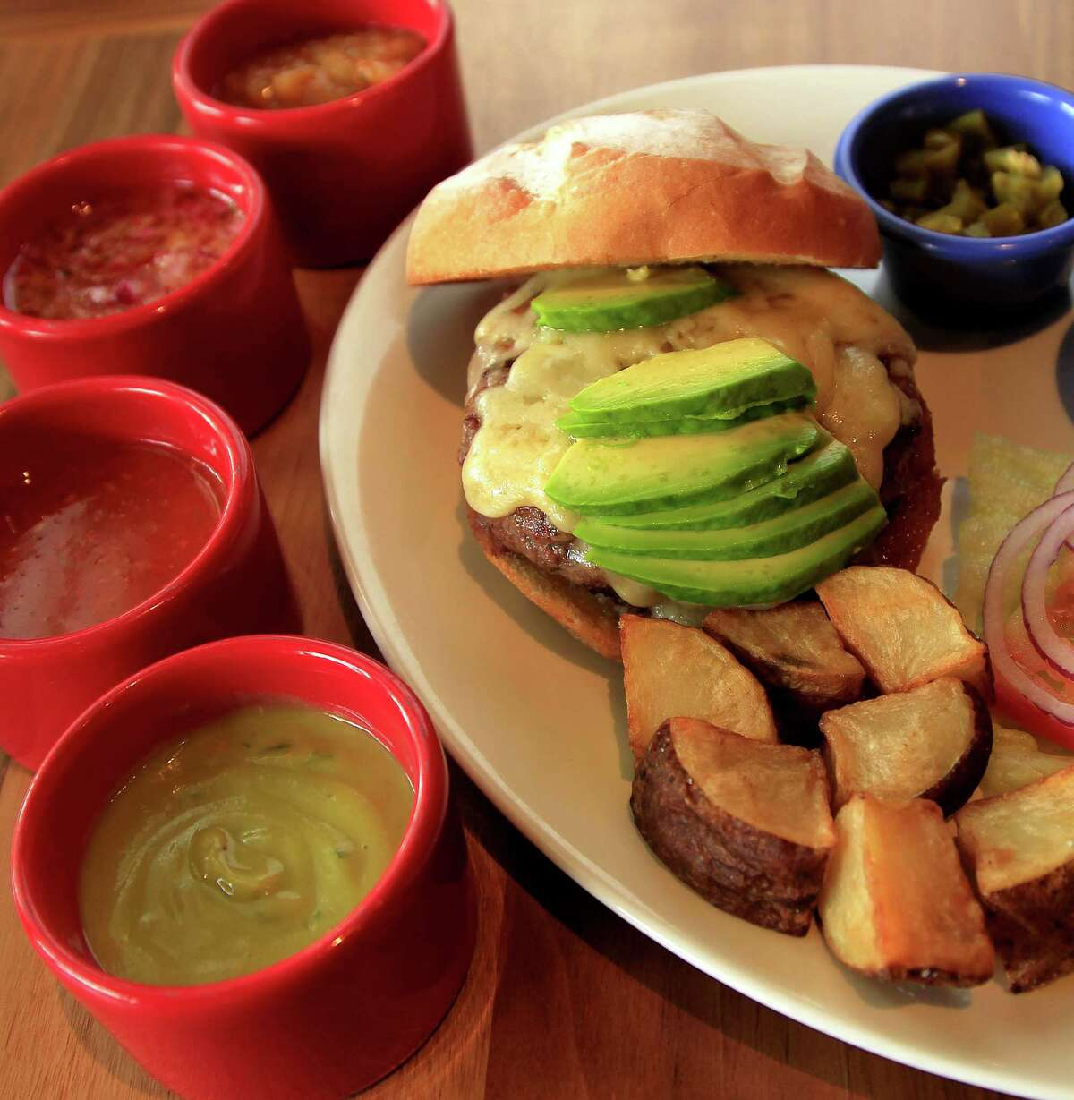 The signature steak burger at La Casa del Caballo, the Mexican steakhouse on lower Westheimer, which features a 10-ounce patty of sirloin and is topped with avocado and Chihuahua cheese. Veggies are optional. It also comes with four different salsas of varying degrees of heat. Photographed, Tuesday, April 22, 2014, in Houston. ( Karen Warren / Houston Chronicle )