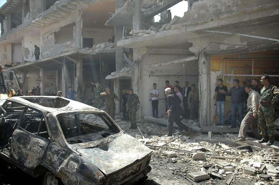 People gather at the site of two car bomb attacks that killed at least 37 at a roundabout in Homs. Photo: Sana, Reuters