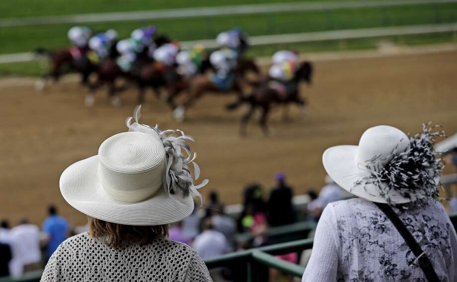 Fans in hats watch a race before the running of the 139th Kentucky Oaks at Churchill Downs Friday, May 3, 2013, in Louisville, Ky. (AP Photo/Charlie Riedel) Photo: Charlie Riedel, Associated Press