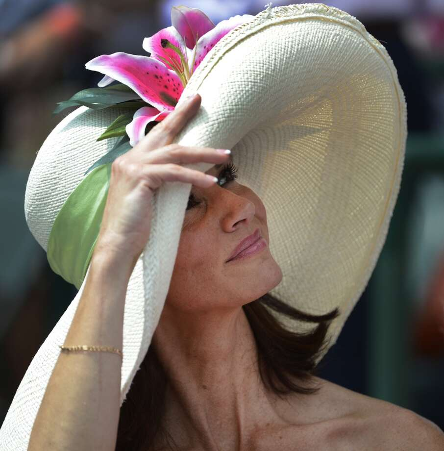 A patron of thoroughbred racing enjoys the sun and the racing atmosphere at Churchill Downs in Louisville, KY. on a day when hats are everywhere the day before the 138th running of The Kentucky Derby May 4, 2012.(Skip Dickstein / Times Union) Photo: SKIP DICKSTEIN, TIMES UNION