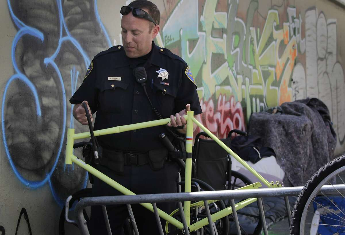 Police officer Matt Friedman checks for the serial number of a bicycle frame while briefly detaining two unidentified men about bikes they were dismantling below the Central Freeway on Duboce Avenue in San Francisco, Calif. on Thursday, May 1, 2014. While police suspect many of the bicycles may be stolen, few arrests are made since owners are reluctant to report them as stolen.