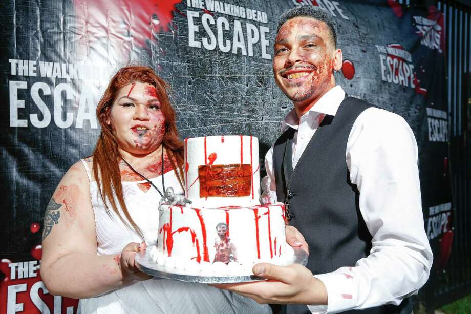 Participants run for their lives from zombies April 26, 2014 in Houston at the Walking Dead Escape at Reliant Stadium. Also Cassie Charlene Hernandez and Andrew Ellis Nieves tie the knot in a zombie wedding.  (Eric Kayne/For the Chronicle) Photo: Eric Kayne / Eric Kayne