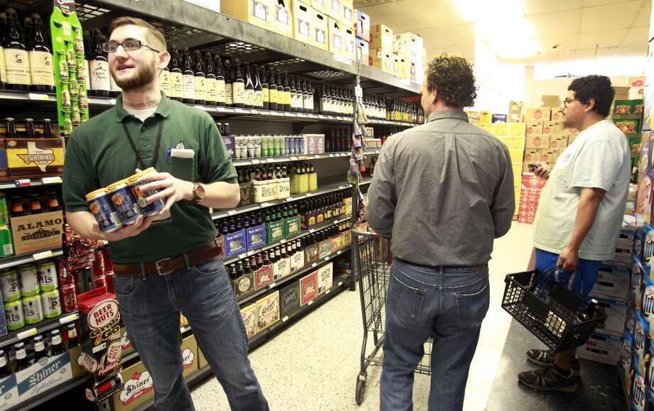 Joey Williams, beer department manager at Spec's, 2410 Smith, talks to customers in the Texas beer section. Before you leave town you should stock up on Karbach and Saint Arnold's Beer. Photo: Melissa Phillip, Houston Chronicle