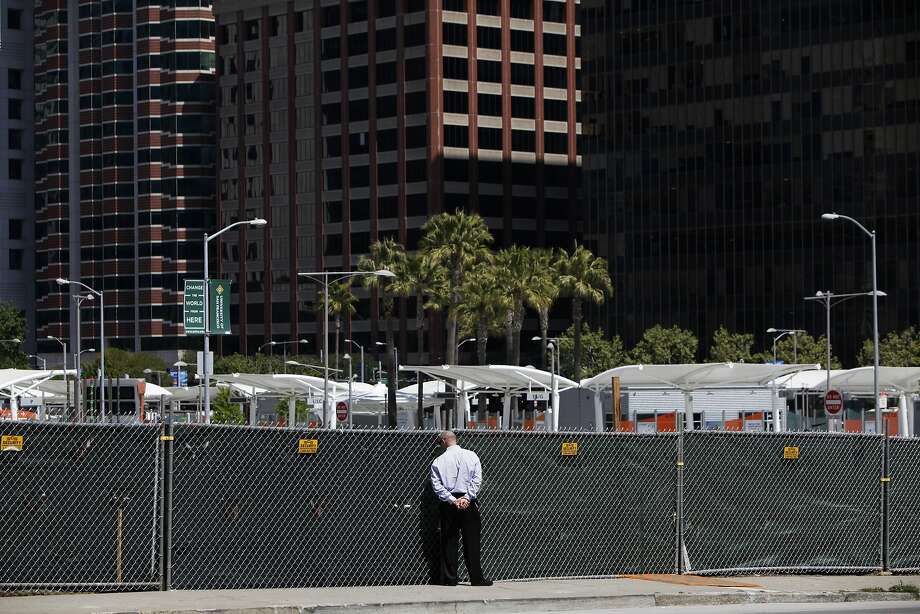 A pedestrian pauses to peer through a fence at a construction site on Folsom Street, where high-rises are going up all around. Photo: Pete Kiehart, The Chronicle