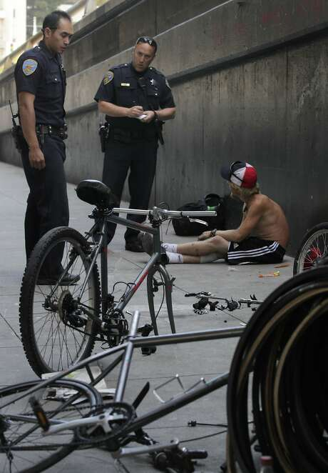 S.F. police Officers Gary Cheng (left) and Matt Friedman question a man about a bicycle he was dismantling. Photo: Paul Chinn, The Chronicle
