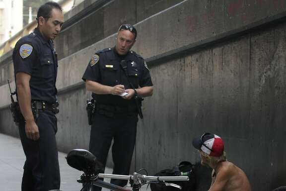 Police officers Gary Cheng (left) and Matt Friedman question an unidentified man about a bicycle he was dismantling below the Central Freeway on Duboce Avenue in San Francisco, Calif. on Thursday, May 1, 2014. The bicycle was not reported stolen, so the man were released. While police suspect many of the bicycles may be stolen, few arrests are made since owners are reluctant to report them as stolen.