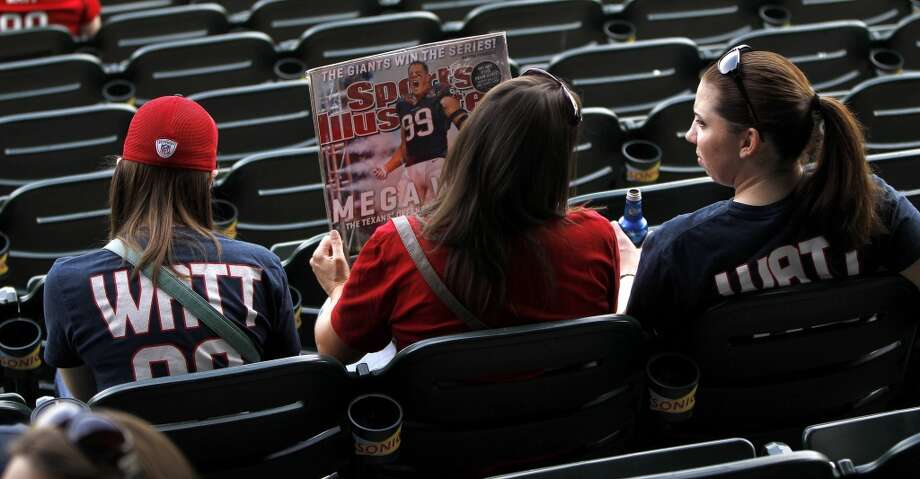 Women sit in their seats with a J.J. Watt Sports Illustrated cover before the start of the game. Photo: Karen Warren, Houston Chronicle