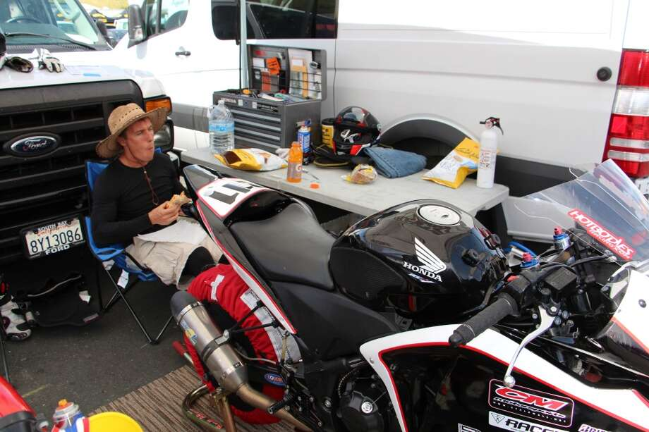 Ari Henning, road test editor of Motorcyclist magazine, taking a lunch break. In front of him is a 2011 Honda CBR250R. The red cloth on the rear tire is a tire warmer, which gets the tires up to a temperature of about 175 degrees. This improves the tire's grip.