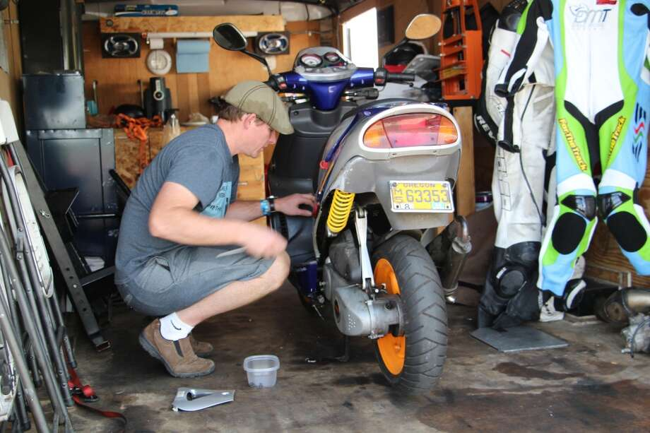 Mike Welch of Medford, Ore., working on a scooter he's fixing for his daughter, Valentine, at the vintage motorcycle races at Sonoma Raceway.  (All photos by Michael Taylor.)