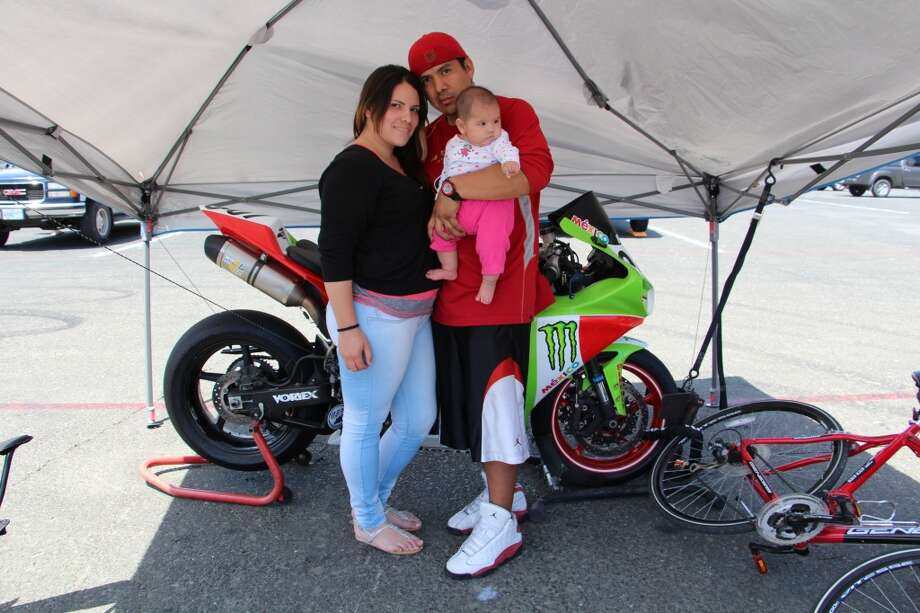Alex Aguilar and Laura Torres, with their four-month-old daughter, Alejandra, all of San Francisco. They're standing in front of his Yamaha R1, painted in the national colors of Mexico.