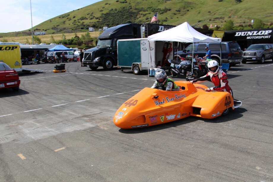 A sidecar rig heads for the track.