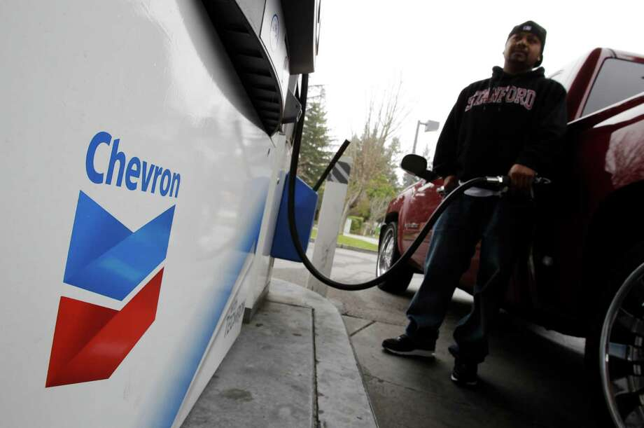 FILE - In this Jan. 28, 2011 file photo, a customer pumps gas at a Chevron gas station in Mountain View, Calif. Chevron Corp. reports quarterly earnings on Friday, May 2, 2014. (AP Photo/Paul Sakuma, File) Photo: Paul Sakuma, STF / AP