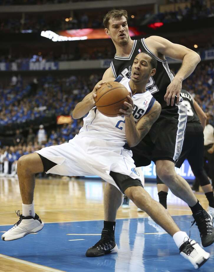 Dallas Mavericks' Devin Harris leans into San Antonio Spurs' Tiago Splitter during the first half of game six in the first round of the Western Conference Playoffs at the American Airlines Center in Dallas, Friday, May 2, 2014. Photo: San Antonio Express-News